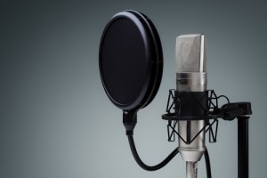 Studio microphone and pop shield on mic stand against gray background